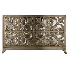 Perfect for displaying a lush floral arrangement or stowing board games and DVDs, this artful sideboard showcases a fleur-de-lis overlay and antiqued mirrore...