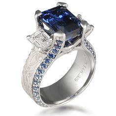 Three Stone Juicy Liqueur Engagement Ring - This luxury engagement ring is a three stone version of the Juicy.   In the main example, an emerald cut blue sapphire is adorned by two trapezoid diamonds . It features mokume gane and pave set diamonds all the way around the band.