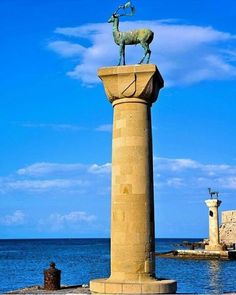 """""""A pair of bronze deer statues flank the inlet to Mandraki Harbor in Rhodes where, according to tradition, the Colossus of Rhodes stood.  Colossus of Rhodes was one of the seven wonders of the ancient world. It was a lighthouse in the form of a giant human figure that straddled the entrance to Mandraki Harbor. Ships entering Rhodes sailed between the legs of the giant. In 226 BC a strong earthquake toppled the Colossus. In its place today are a pair of statues of the symbol of Rhodes - a…"""
