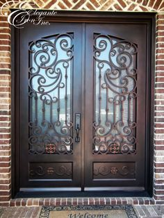 Custom wrought iron front door with scrollwork and medallions on footboard.