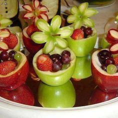 What a fun way to get your kids to eat their fruits! Make a bowl out of an apple and fill it with berries and grapes! Yum :)