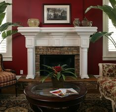 This red accent wall is bold, but a great look in this particular living room. The white trim, green plants and patterned furniture make it work.