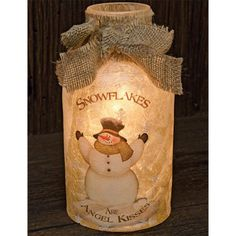 Lighted glass jar features a painted Snowman on a frosted glass with burlap tie accent around the mouth of the jar. A 10 count electric white light strand lights up the inside of the jar. 8-3/4inches
