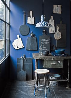 Using different shapes of cutting boards and having them hung against blue wall.