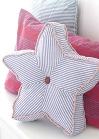 Perk up a porch chair with this starry  pillow. Sewn from separate diamonds of fabric, the cover highlights  seersucker's trim stripes.  A vintage  red button punctuates the center