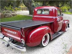 Maroon 49'-51' Chevy 3100 on baby moons from 3/4 rear