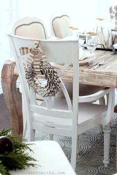 The House of Smiths - Small metallic pine cone wreath with striped ribbon over captains chairs