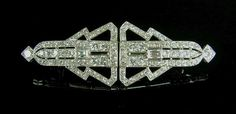 White metal Art Deco diamond double clip brooch, tests 18 ct gold. Comprising two clips of geometric design each set with a central baguette cut diamond and forty seven round brilliant cut diamonds. The two clips attach to form one larger clip by way of a separate framework. Total estimated diamond weight 4.50 cts. Total length 65 mm / 2.5 in. Total weight 14.6 grams.