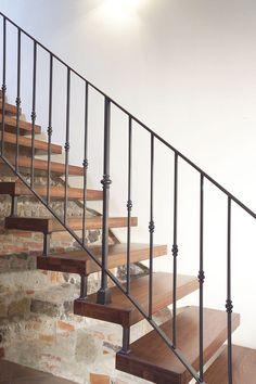 escalier en bois à barreaudage en fer forgé et mur en brique
