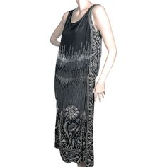 Gorgeous late 1920s flapper dress.  The height of 1920's opulence in heavy black silk beaded flapper dress, featuring extraordinary clear and iridescent white seed bead work. The drop waist is ruched on both sides, one side has a dramatic beaded swag panel.