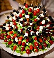 Kabobs with tomatoes, olives, mozzarella and cucumber on a bed of lettuce. Great idea!
