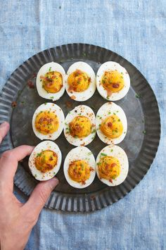 I have updated my deviled eggs by adding some sriracha, curry powder and bacon. All three flavors come together to create a smooth, spicy and hearty deviled egg.
