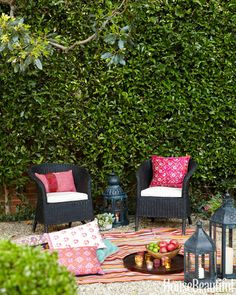 """Tour a Los Angeles Cottage with """"Granny-Chic"""" CharmCrate & Barrel wicker chairs, Pat McGann pillows, Nathan Turner lanterns, and a flea-market rug make the backyard an irresistible outdoor retreat."""