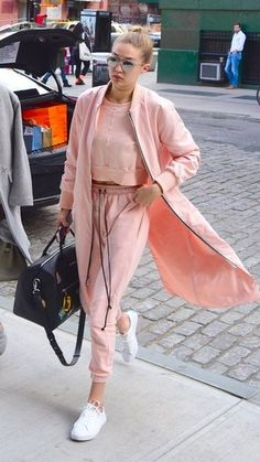 Gigi Hadid in an all pink sweat suit with bright white sneakers.
