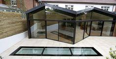 minimally framed sliding glass doors sliding away from odd angles, walk on glass floorlight to basement