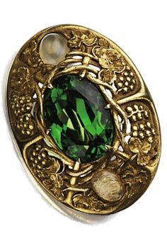 An Arts and Crafts gold, peridot and opal brooch, Tiffany & Co., circa 1910. Centring an oval-shaped peridot within a gold frame chased with meandering grape clusters and leaves, the sides set with 2 oval-shaped opal cabochons, signed Tiffany & Co. Probably designed by Louis Comfort Tiffany.