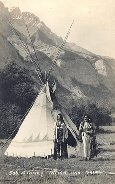 The photo caption identifies this as a Stoney (Nakoda) couple, although the painted design on the tipi is typically Blackfoot. Probably located in the Rocky Mountains of western Alberta, Canada. n.d. JE