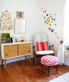 unique fabric covers on chair, pillow, and ottoman, cute dress as decor on wall, retro cabinet makes a fun and eclectic kid's bedroom.