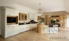 A timeless combination of soft cream hand painted cabinets, oak furniture and dark worktops and splash back.
