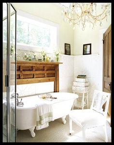 Claw foot tub, terry cloth covered chair, antique mantle to frame tub and provide a little ledge to put things on, and floors tiled with those cute hexagon pieces.  Love the chandelier, of course.