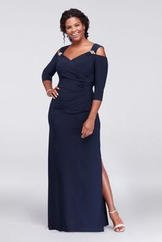 This sleek plus-size jersey sheath gown stays on-trend with crystal-accented cold shoulder details. Side ruching and a faux-surplice neckline provide figure-flattering detail.   By R&M Richards  P