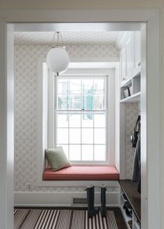 Transitional mudroom features walls clad in white and beige fan print wallpaper framing a built-in window seat