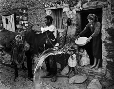 """Eugene Smith - A farmer unloads his donkey in front of his home. His wife throws out the dirty dishwater. / From """"Spanish Village"""" photo-essay. War Photography, Photography Projects, Documentary Photography, Equatorial Africa, Eugene Smith, Isadora Duncan, Village Photos, Pittsburgh City, Photo Report"""