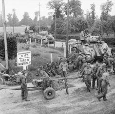 2 août 1944, chars Sherman et canons de 6 pdr britanniques à Saint-Charles-de-Percy. On aperçoit des prisonniers allemands rassemblés sur le bord de la route. (IWM).