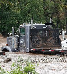The overflowing St. Vrain River swamps parked semi trucks following overnight flash flooding, one mile east of Lyons, Colo., Thursday, Sept 12, 2013.