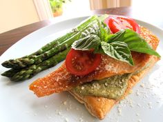Seared salmon is served over a freshly baked puff pastry, topped with creamy pesto sauce, tomatoes, basil, and cheese. Kosher, Shavuot.