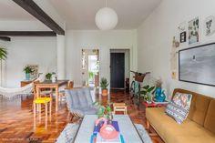 Sala de estar tem uma mistura de peças de design e seleção bacana de objetos de decoração.
