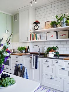 White kitchen with light wood counters and a white subway tile backsplash Country Kitchen, New Kitchen, Kitchen Dining, Kitchen Decor, Kitchen Hair, Kitchen White, Kitchen Things, Kitchen Sink, Beautiful Kitchens