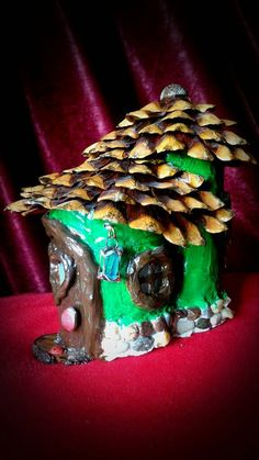 Beautiful fairy cottage, designed to blend in with the green surroundings. Fairies are clearly visiting for the summer, but they dont pay rent. They do tend to our flowers and we always have blooming pots, so we let them slide. 8.7 inches long 6.7 inches tall 4.7 inches wide  This house is made using cardboard as a shape, then plastered and painted with acrylic colors, then 2-3 layers of varnish. The roof top is natural pine cone scales, also double varnished. It is best not to be hold…