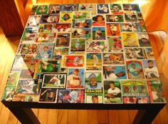 I need to do this with all my cards  Baseball card table....dollar tree sells a bag of about 100plus baseball cards for a buck..der...you could use a couple bags of those to make this table...plus mod podge then  clear shellac on it..