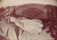 A matt silver gelatin print, probably dating from the 1890's or perhaps shortly after, showing a young girl laid out on a sofa. An inked inscription on the reverse of the mount reads Genevie Cox Plainfield / Taken when she was dead.    Photographed by M. Tomlinson of Plainfield, Indiana, identified by details printed crudely on the reverse of the mount.