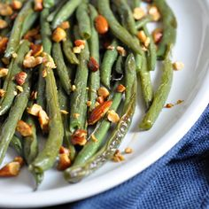 Fresh green beans are roasted with seasonings until crisp tender, then topped with Sriracha Almonds for a little added kick!
