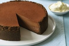 Chocolate cheesecake Ingredients: Melted butter, to grease 1 x 250g pkt plain chocolate biscuits, coarsely broken 1/2 tsp ground cinnamon 150g butter, melted 250g dark chocolate, finely chopped 155g (3/4 cup) caster sugar 3 eggs 3 x 250g pkts cream cheese, at room temperature 2 tbs cocoa powder, sifted 1 tsp vanilla essence 2 x 300g ctns sour cream Cocoa powder, extra, to serve Double cream, to serve