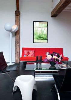 A black and white living with a red sofa