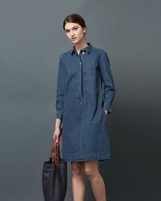 Shirt dress with large patch pocket in lovely and supple, real indigo-dyed, washed denim - washed for a lighter shade of indigo. Soft, neat collar. Corozo shank buttons. Double buttoned cuff. Split side seams. Box pleat into back yoke.