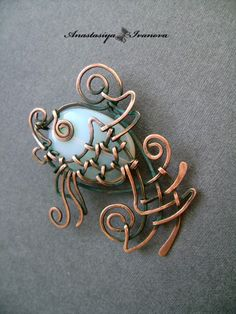 A wire fish pendant. Love how the bead is the body of the fish.