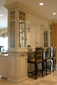 Fancy glass cabinets separate the kitchen from the dining area and create a bar seating area.