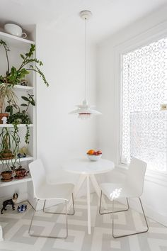 A Pair of Designers Renovate Their Brooklyn Brownstone With a Bright Monochromatic Palette - Photo 7 of 12 - In the kitchen, a PH 50 pendant by Poul Henningsen for Louis Poulsen hangs overhead; the window is covered in a decorative cast-iron metal security grate from King Architectural Metals. The painted patterned floor is by Lillian Heard Studio.