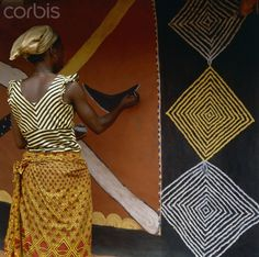 Africa   'Woman Painting a Mural'   Nwunnan uses natural pigments to decorate the wall of a village dwelling. Her pattern on her blouse echoes that of the traditional, diamond-shaped, motif, known as ogalu, which is incorporated into the mural. Nri, Nigeria.   © Margret Courtney - Clark
