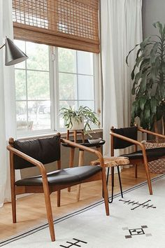 The Lento black leather lounge chair is made from solid, walnut-stained wood frame. Photo by Maggie Miller Interiors. #ModernLoungeChair #LivingRoomInspo #ModernLivingRoom