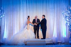 Wedding ceremony on a white draped stage in the ballroom. All white decor with blue lighting by Asiel Designs. Feathers, crystals, mirror glass, large lace tablecloths. Photographed at the Ritz-Carlton, Half Moon Bay. San Fransisco, Bay Area, Destination Wedding.
