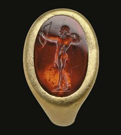 A c.first-century AD Roman gold and garnet ring set with a flat garnet, engraved with the figure of the sun god Apollo, with bow-and-arrow and wreath symbolic attributes. (Christie's)