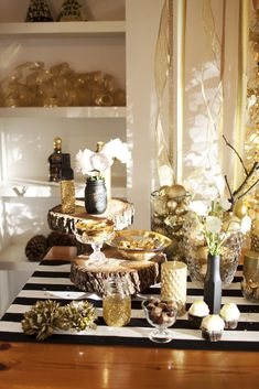 Buffet display with black and white stripes, matte black mason jars, gold glitter mason jars, rustic wood cake stands, vases filled with gold baubles, birch branches, white paper flowers