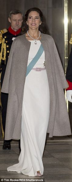 Adding interest to the otherwise demure dress, Mary tied a blush-pink coloured belt around her waist and hung a taupe overcoat on her shoulders as she made her way into the halls ofCopenhagen's Christiansborg Palace