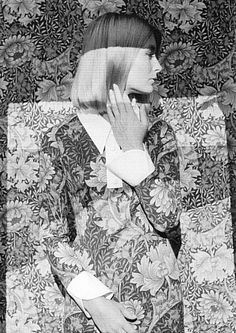 A woman modelling a three-quarter-length dress blends in with a background of identical floral-print fabric, ca. 1966. Photo by Duffy/Getty Images. °