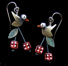 The most important aspect of Lisa and Scott Cylinder's jewelry designs is the imagery.  It has narrative themes based upon fables, play on words, and observations.  Within most of these tales are movable elements; free swinging legs and dangling fruit or fish.  The feel it is the kinetic facet that gives their jewelry its charm and character.